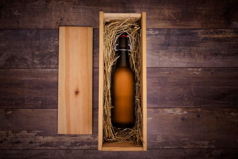 Basteln-Sie-Bierflasche-in-einer-holzernen-Geschenkbox-auf-einem-rustikalen-Tisch