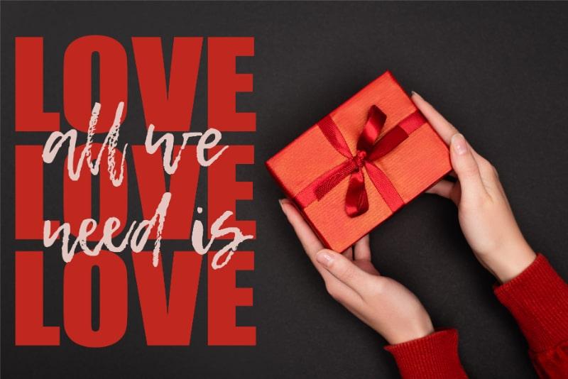 Beschnittene-Ansicht-der-Frau-die-rotes-Geschenk-nahe-alles-halt-was-wir-brauchen-ist-Liebesbeschriftung-auf-Schwarz
