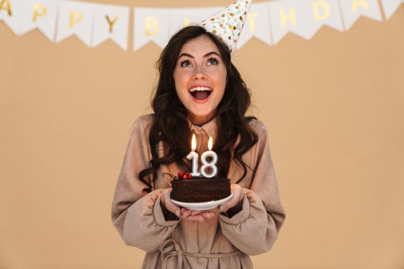 Bild-der-aufgeregten-jungen-Frau-im-Partykegel-lachelnd-beim-Aufstellen-mit-Geburtstagstorte