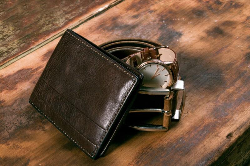 Brieftasche-Uhr-und-Gurtel-auf-Holztisch