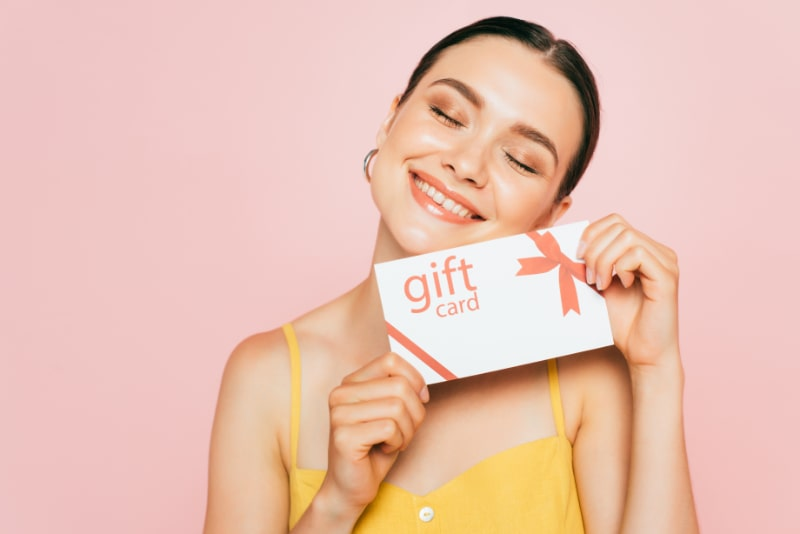 Brunette-junge-Frau-mit-geschlossenen-Augen-die-Geschenkkarte-halten