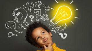 Denkender Kinderjunge auf schwarzem Hintergrund mit Glühbirne und Fragezeichen. Brainstorming und Ideenkonzept