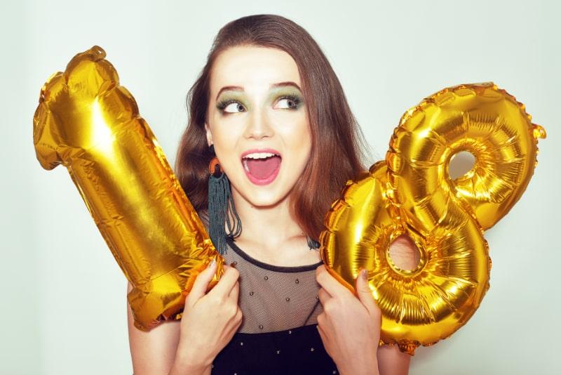 Ein-Geburtstagskind-an-ihrem-18.-Geburtstag-mit-goldenen-Zahlenballons.