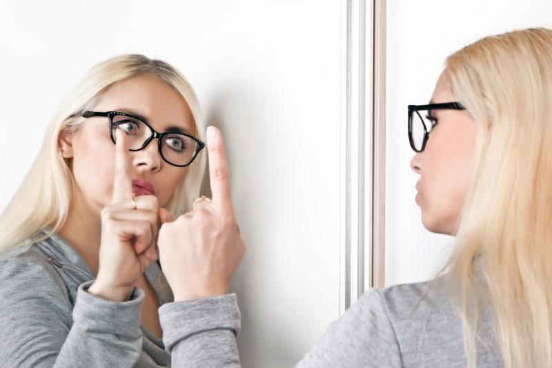 Eine-Frau-spricht-vor-einem-Spiegel-mit-ihrem-Spiegelbild.
