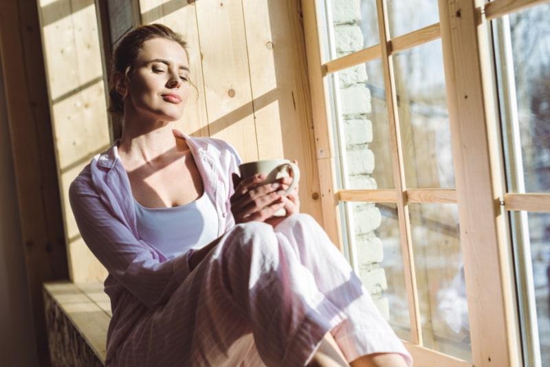 Frau-sitzt-am-Fenster-im-morgendlichen-Trinkcaffee