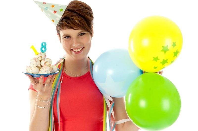 Frau-wird-18-und-halt-Kuchen-und-Ballons