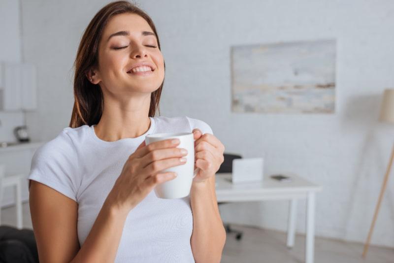 Frohliche-Frau-traumt-beim-Halten-der-Tasse-Tee