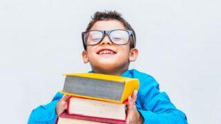 Fröhlicher Junge in Gläsern mit Büchern am Schreibtisch