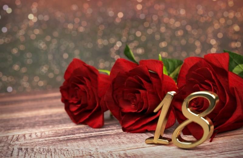 Geburtstagskonzept-mit-roten-Rosen-auf-holzernem-Schreibtisch.-achtzehnten.-18-..