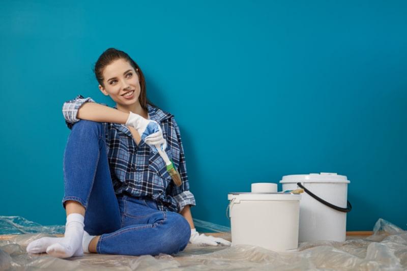 Gluckliche-schone-junge-Frau-die-Wandmalerei-tut