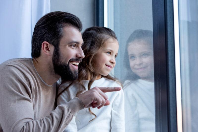 Glucklicher-Vater-der-auf-etwas-zeigt-und-wegschaut