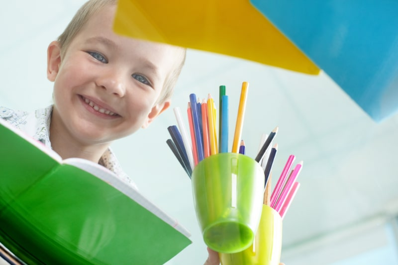 Gluckliches-Gesicht-eines-Jungen-der-durch-einen-Tisch-schaut-auf-dem-Tisch-viel-bunte-Bleistifte