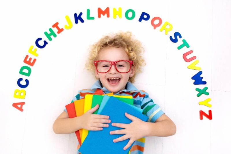 Gluckliches-Vorschulkind-das-das-Lesen-und-Schreiben-lernt-und-mit-bunten-Buchstaben-spielt