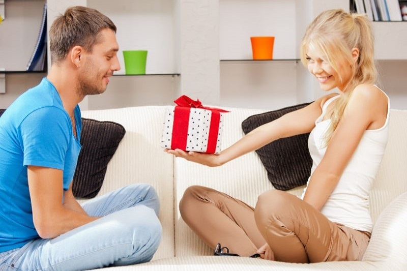Gluckliches-romantisches-Paar-mit-Geschenk