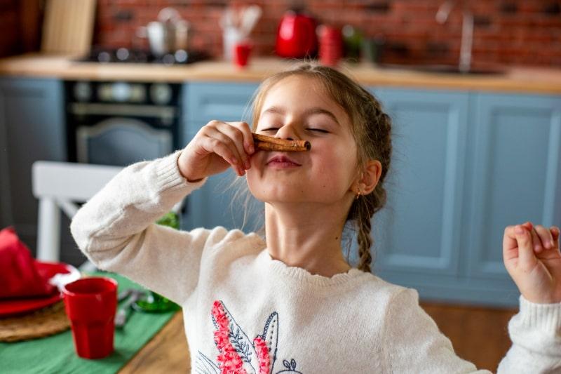 Gluckliches-sechsjahriges-Madchen-mit-Vergnugen-das-eine-Zimtstange-schnuffelt