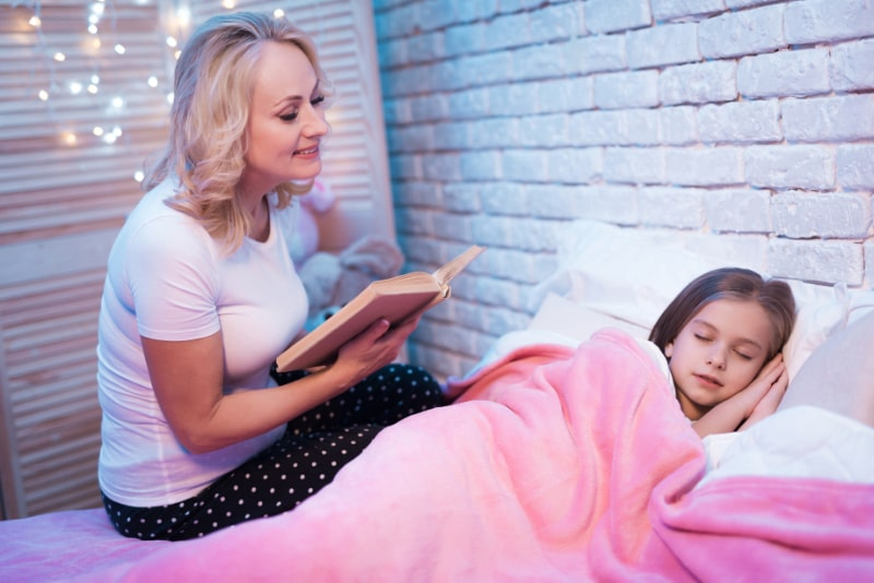 Grosmutter-liest-Buch-wahrend-Enkelin-zu-Hause-im-Bett-liegt
