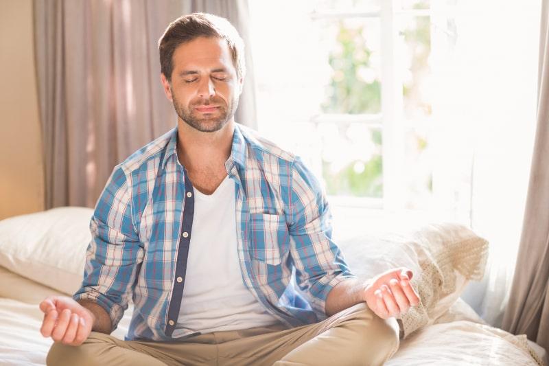 Hubscher-Mann-der-Yoga-auf-Bett-tut