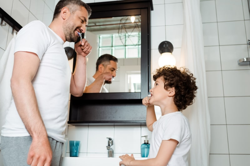 Hubscher-Vater-und-lockiger-Sohn-die-Zahne-im-Badezimmer-putzen