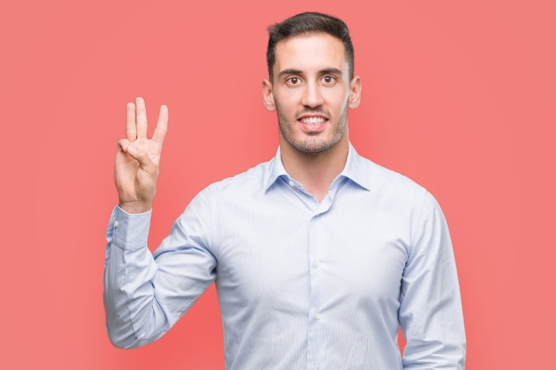 Hubscher-junger-Geschaftsmann-der-mit-den-Fingern-Nummer-drei-zeigt-wahrend-er-selbstbewusst-und-glucklich-lachelt.-1