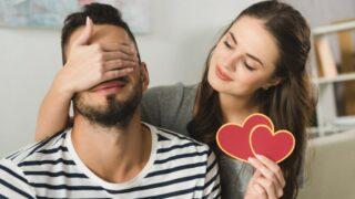 Junge Frau, die Augen des Freundes mit Hand bedeckt und Valentinstaggrußkarte hält