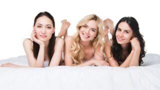 Junge schöne Frauen, die auf Bett liegen