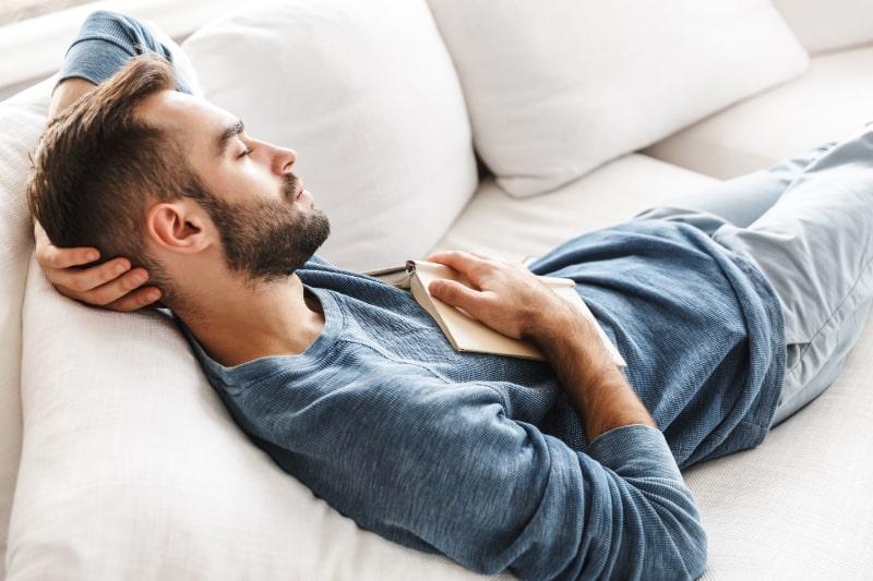 Junger-Mann-der-mit-Buch-zu-Hause-schlaft