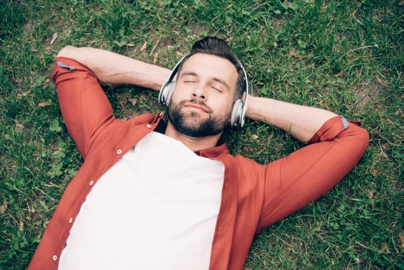 Junger-Mann-mit-geschlossenen-Augen-die-auf-Gras-mit-den-Handen-hinter-dem-Kopf-liegen-und-Musik-horen