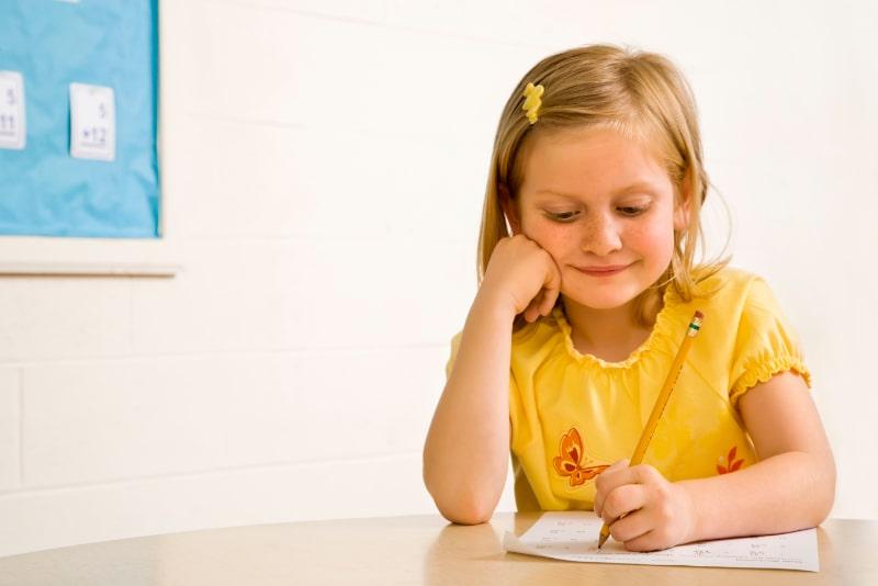 Junges-Madchen-lachelnd-im-Klassenzimmer-Schreiben-auf-Papier