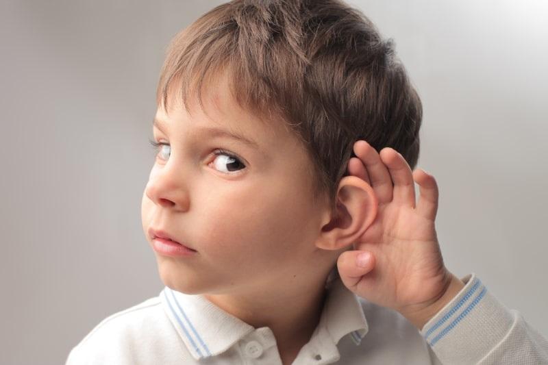 Kind-Junge-der-versucht-etwas-zu-horen