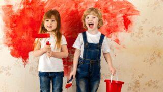 Kinder Maler. Kleine Künstler mit einem Pinsel in der Hand und einem Farbroller mit roter Farbe auf der Tapete im Raum an der Wand.