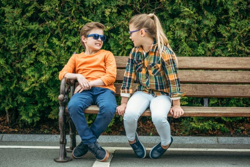 Kinder-sitzen-auf-Bank
