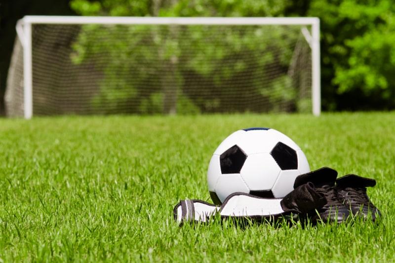 Kindersportkonzept-mit-Fusball-Stollen-Schienbeinschoner-auf-dem-Feld