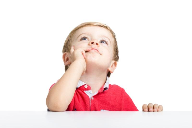 Kleiner-Junge-der-am-weisen-Tisch-steht-und-aufschaut