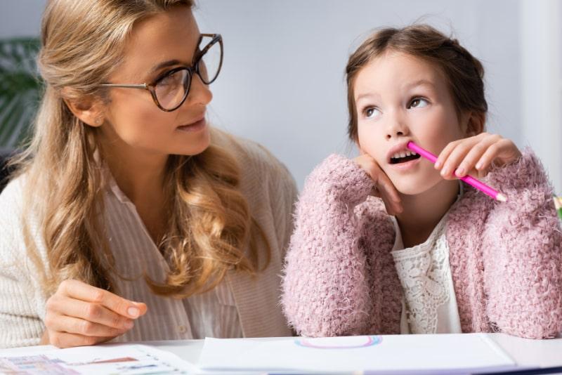 Kleines-Madchen-das-Bilder-mit-bunten-Stiften-zeichnet-wahrend-es-neben-ihrer-Mutter-sitzt