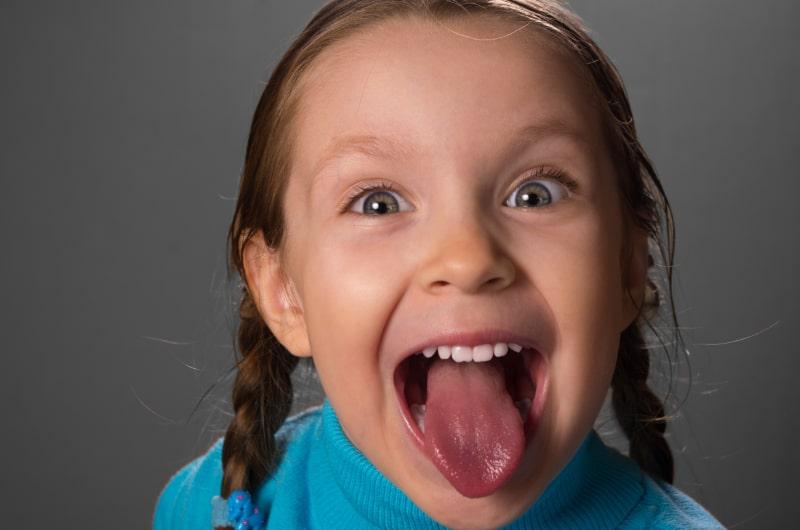 Kleines-Madchen-das-die-Zunge-zeigt.