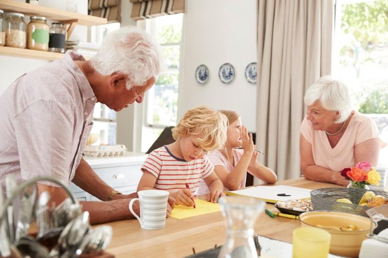 Lachelnde-Groseltern-mit-Enkelkindern-in-der-Kuche