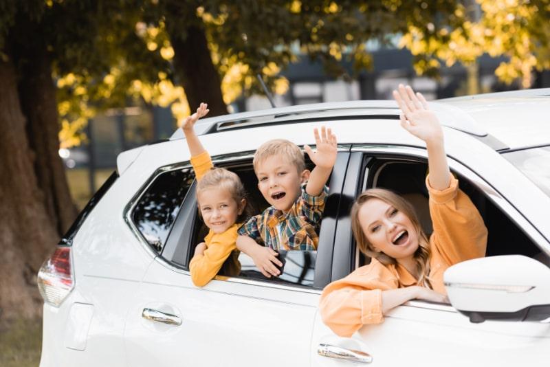 Lachelnde-Kinder-die-Hande-nahe-Mutter-wahrend-der-Reise-im-Auto-winken