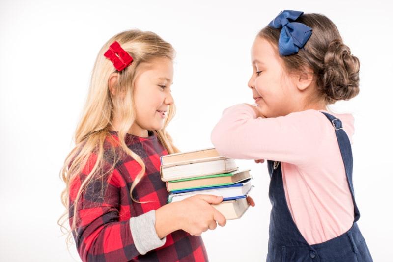 Lachelnde-Schulmadchen-die-mit-Buchern-stehen