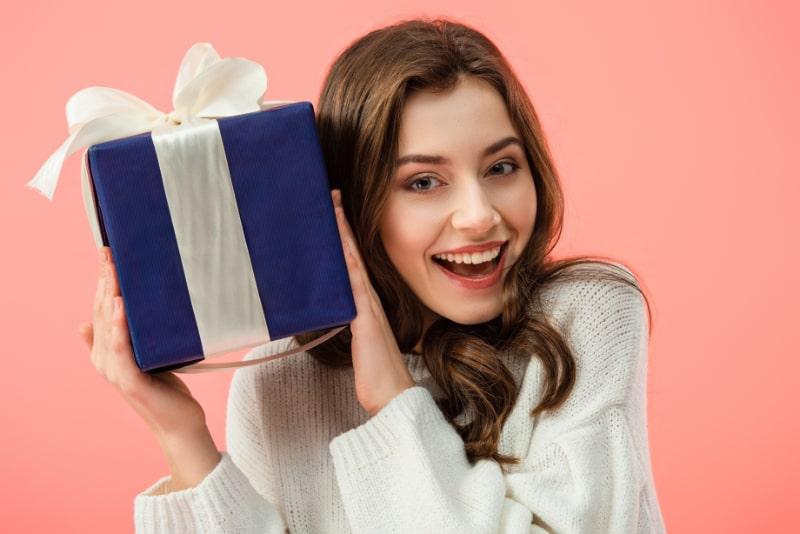 Lachelnde-und-schone-Frau-im-weisen-Pullover-der-Geschenkbox-halt