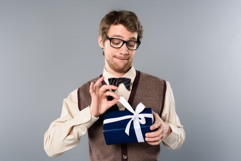 Lustiger-Mann-in-den-Glasern-die-Bogen-auf-Geschenkbox-losen