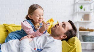 Mädchen, das Spielzeugotoskop nahe Vater hält, der auf Sofa mit geschlossenen Augen liegt