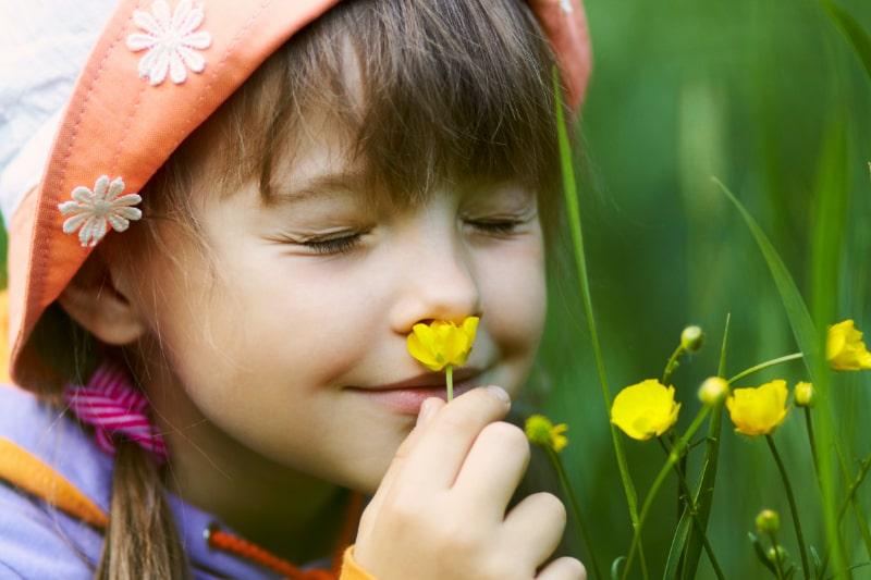 Madchen-riecht-an-einer-Blume