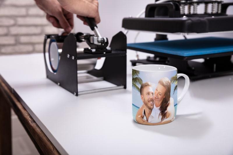 Mann-der-auf-Kaffeetassen-in-der-Werkstatt-druckt