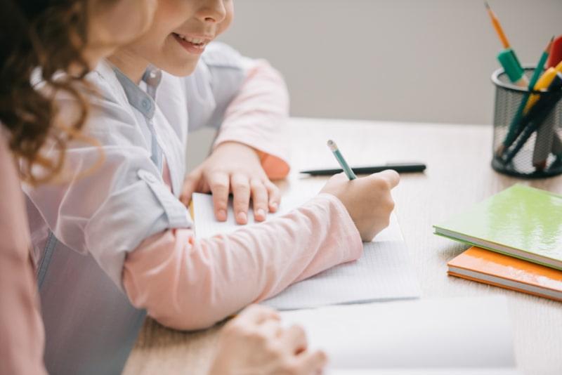 Mutter-und-Tochter-sitzen-am-Tisch-und-machen-zu-Hause-gemeinsam-Schularbeiten