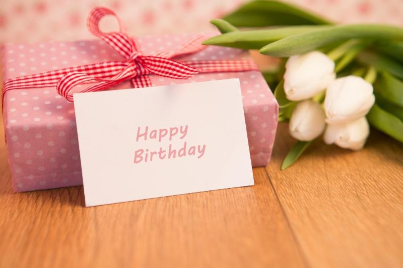 Rosa-verpacktes-Geschenk-mit-Bundel-weiser-Tulpen-und-alles-Gute-zum-Geburtstag