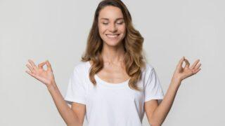 Ruhige ruhige Frau, die Yogaübungen auf weißem leerem Hintergrund tut