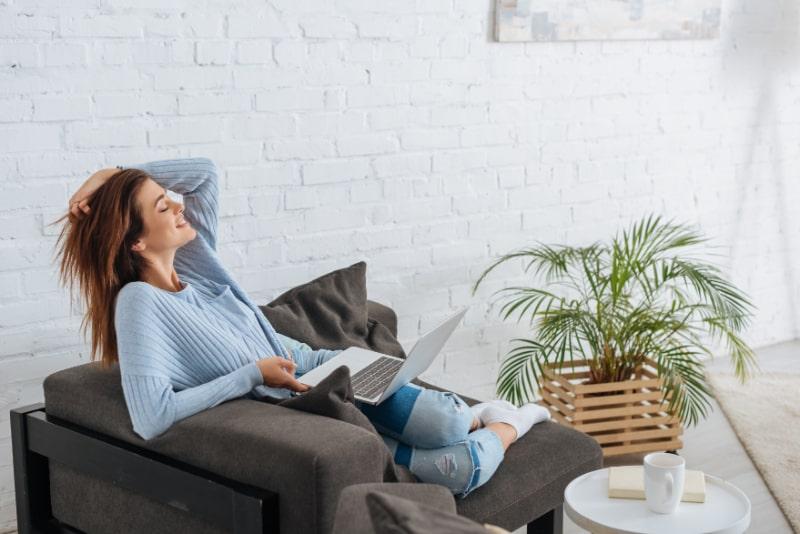 Seitenansicht-der-glucklichen-Frau-die-mit-Laptop-zu-Hause-kuhlt
