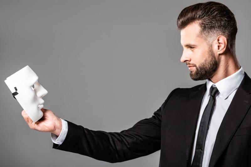 Seitenansicht-des-zuversichtlichen-Geschaftsmannes-im-schwarzen-Anzug-der-Maske-betrachtet-die-auf-Grau-lokalisiert-ist