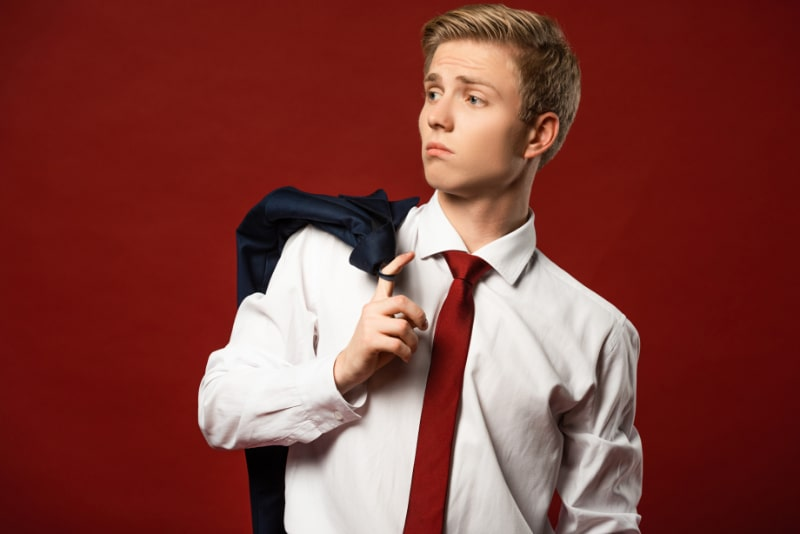 Selbstbewusster-Mann-mit-Jacke-am-Finger-auf-rotem-Hintergrund