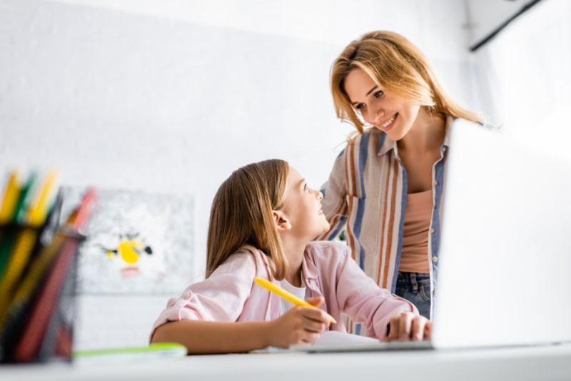 Selektiver-Fokus-des-lachelnden-Kindes-das-Mutter-wahrend-der-Online-Bildung-zu-Hause-betrachtet